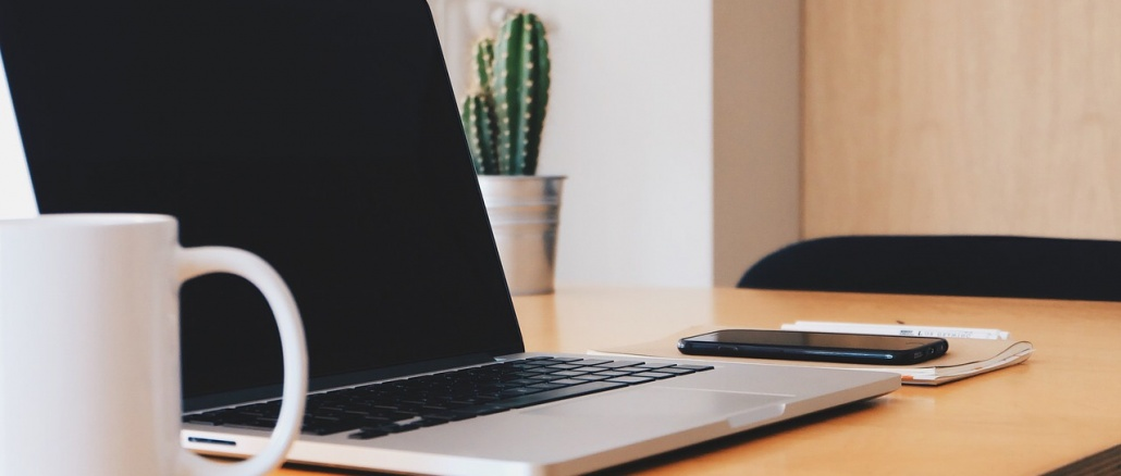 Desk with laptop, coffee cup, and plants. Represents business related events and information. Credit: StockSnap/Pixabay