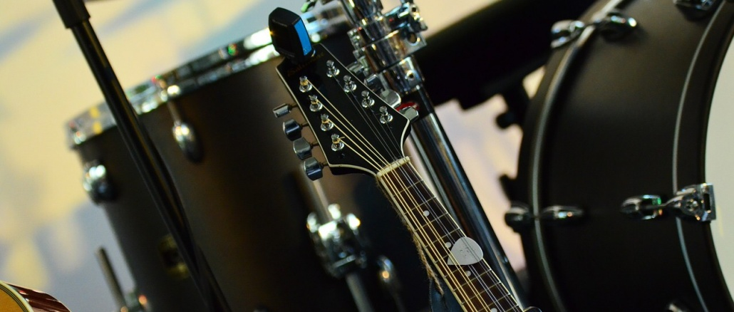 Drum set with partial guitars showing. Image for live music, local bands, jam sessions.