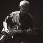 Either dim-lighting or black and white image of Dave Sadler playing guitar. Credit: John David Pittman