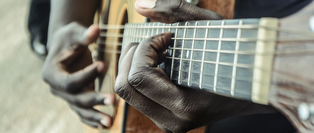 Image showing close-up of acoustic guitar played by hands of African-American man. Represents Acrican-Americans, lack history, and/or music. Credit: sycline/Pixabay